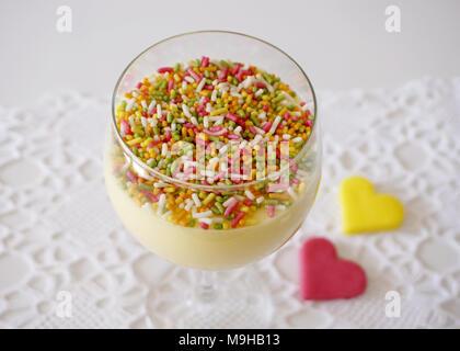 Vanille Creme im Glas dekoriert mit bunten Streuseln oben und zwei herzförmige Plätzchen auf dem Hintergrund - Stockfoto