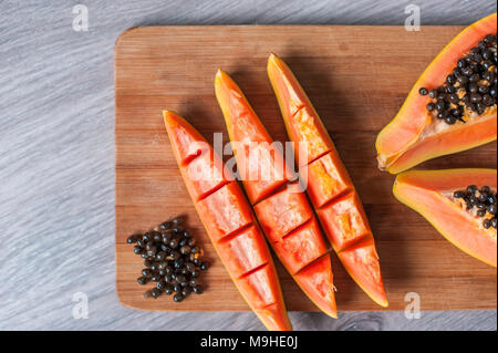 Papaya Frucht in Scheiben geschnitten auf hölzernen Hintergrund - Stockfoto