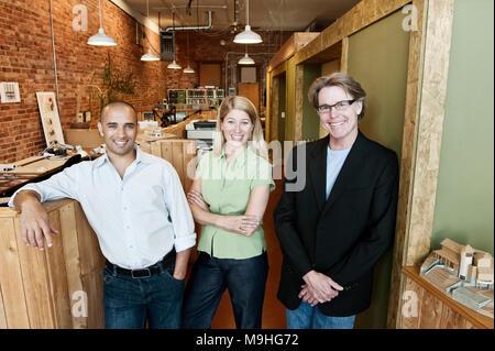 Porträt einer multi-ethnischen Team von drei Architekten, die in einem kleinen Büro. - Stockfoto