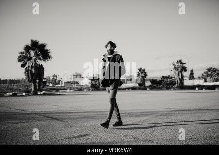 Junger Mann mit langem Bart zu Fuß und in der Stadt Vorstädten mit Casual Style Kleidung posieren. Schwarz und Weiß. - Stockfoto