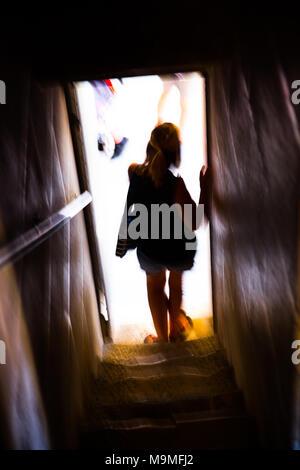 Silhouette einer Frau in einem Türrahmen über zu Schritt in einer geschäftigen Stadt - Stockfoto