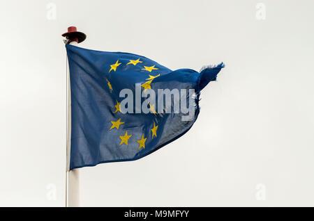 Eine Abgerissene und beschädigte die Europäische Union (EU) Flagge weht im Wind gegen einen weissen Himmel. - Stockfoto
