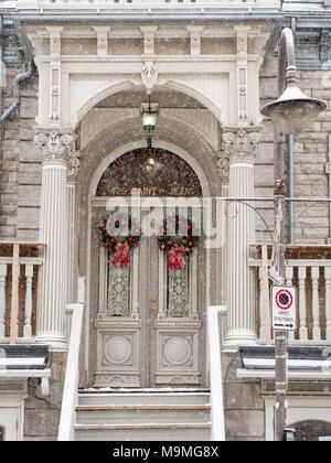 Ein paar der dekorierten Türen im Schnee: Der Eingang zu 429 Saint Jean durch zwei passende Kränze über die doppeltüren eingerichtet. Fancy Säulen und einer Veranda aus dem fallenden Schnee zu schützen. - Stockfoto