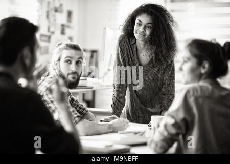 Treffen Im. eine schwarze Frau im Gespräch mit Ihren Kollegen - Stockfoto