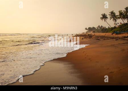 Leeren Strand am Nachmittag Sonne, Sand nass von Wellen, mit Schattenrissen von Personen spielen in den Hintergrund. Kalutara, Sri Lanka - Stockfoto