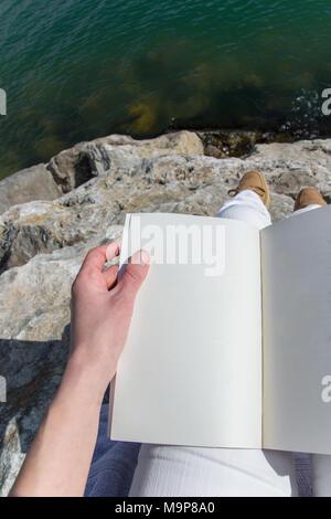 Oben auf die Hand eines erwachsenen Menschen halten, sitzen auf dem Meer Felsen - Stockfoto