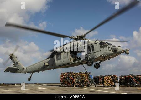 180324-M-RT 059-0547 ÄGÄIS (24. März 2018) Segler auf die Harpers Ferry zugeordnet - Klasse dock Landung Schiff USS Oak Hill (LSD 51) Haken Artikel für den Transport auf einem MH-60S Seahawk Helikopter Hubschrauber Meer Combat Squadron (HSC) 28, während eine Auffüll-anforderung-auf-See in der Ägäis März 24, 2018 zugeordnet. Oak Hill, Home-in Virginia Beach, Virginia portiert, und der 26. MEU leiten naval Operations in den USA 6 Flotte Bereich der Operationen. (U.S. Marine Corps Foto: Staff Sgt. Dengrier M. Baez/Freigegeben) - Stockfoto