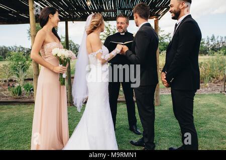Braut und Bräutigam vor der Priester Zeugnis der Brautjungfern und bester Mann. Hochzeit im Freien Zeremonie der schönes Paar. - Stockfoto