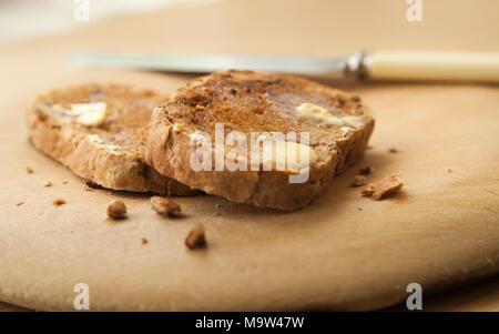 Zwei Scheiben warm nussig Artisan Brot getoastet mit Butter schmelzen auf Holzbrett mit einem Messer aus der Schwerpunkt neben der Schichten. - Stockfoto