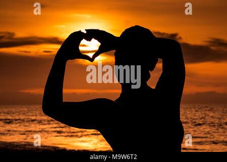 Silhouette von jungen Mädchen mit Sonnenuntergang am Strand, die Form eines Herzens mit den Händen bilden. - Stockfoto