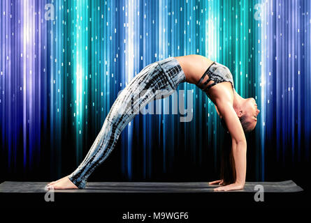 Fit athletische Frau Demonstration einer geraden Beinen Rad stellen während der Arbeit aus Yoga wölbt den Rücken mit Füßen und Händen auf der Matte in einer Seite v - Stockfoto