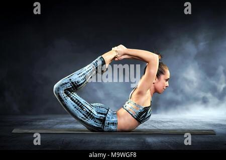 Athletische Frau Demonstration der Bogen im Yoga in einer Nahaufnahme Seite Blick auf einem schwarzen Hintergrund mit Rauch - Stockfoto