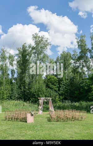 Schöne Einstellung für freien Trauung warten auf Braut und Bräutigam und Gäste. Stühle aus Holz, geschmückt mit Blumen, befinden sich in der Zone der Trauung in einem Wald - Stockfoto