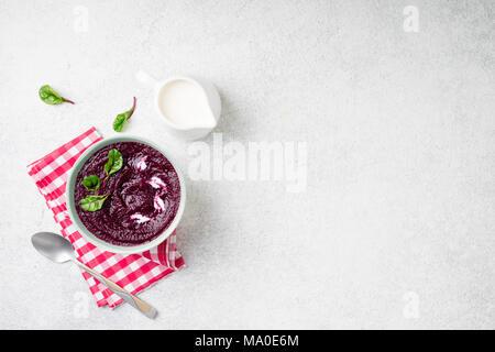Rote-bete-Cremesuppe in Schüssel am weißen Stein Hintergrund. Detox Rote-beete-Püree Smoothie mit Mangold verlässt. Das Nähren, sauber Essen, abnehmen, vegetarische fo - Stockfoto
