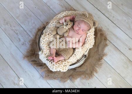 Sechs Wochen altes Baby Boy trug eine beige, andere als aus Gewirken, tragen Motorhaube. Er schläft mit einer passenden Teddybär. Im Studio Shot auf hellem Holz backgroun - Stockfoto