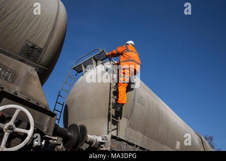 Eine Eisenbahn Wartung Arbeiter tragen Hi viz Kleidung klettern eine Leiter auf eine Profilschiene Tanker das obere Deck während Arbeiten in großer Höhe zu prüfen. - Stockfoto