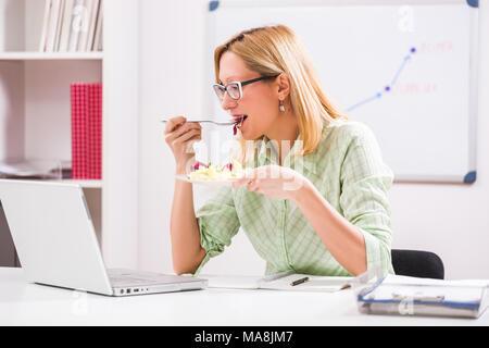 Geschäftsfrau ist Salat in Ihrem Büro. - Stockfoto