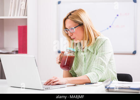 Geschäftsfrau ist Trink Smoothie in Ihrem Büro. - Stockfoto