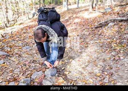 Junger Mann auf Wanderweg durch orange Laub Herbst Herbst Wald binden Schuhe Sneaker mit viele Blätter auf dem Weg in Harper's Ferry, West Virginia - Stockfoto