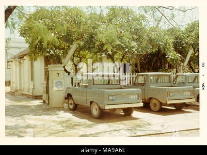 Farbfoto, zeigen drei Ford Pickup Trucks vor einem lattenzaun geparkt, mit Bäumen und einem weißen Haus im Hintergrund, die in Vietnam während des Vietnam Krieges fotografiert (1955-1975), 1968. () - Stockfoto