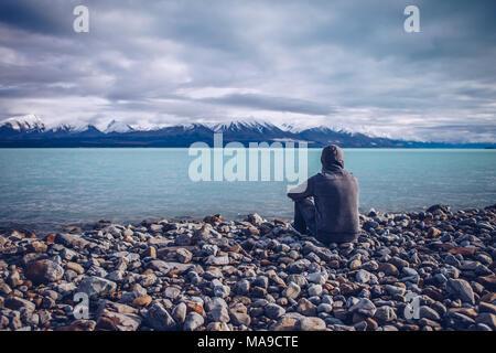 Junger Mann mit Blick auf den See Tekapo und die schneebedeckten Berge in Neuseeland - Stockfoto