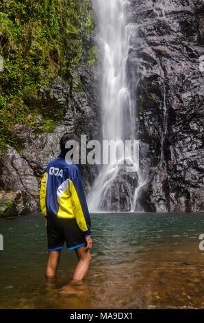 """Rückansicht eines Jungen tragen"""" Goa'Jacke, stehend in knietiefem Wasser, Blick auf die mächtigen Mainapi Wasserfall in Netravali Wildlife Sanctuary, Goa. - Stockfoto"""