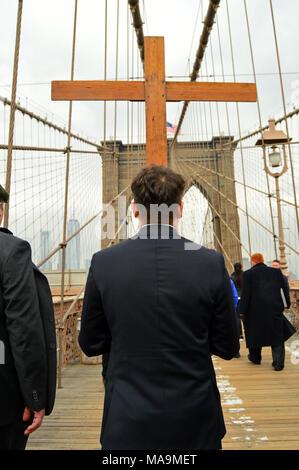 New York, NY, USA, 30. März 2018 ein junger Mann trägt ein hölzernes Kreuz über die Brooklyn Bridge, als Teil einer Karfreitagsprozession in New York Credit: James Kirkikis/Alamy leben Nachrichten - Stockfoto
