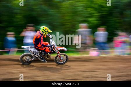 Uschhorod, Ukraine - 21. Mai 2017: Junior MX rider schaltet auf eine Ecke. Motion Blur mit fliegenden Schmutz. Transkarpatische World Motocross Championship - Stockfoto