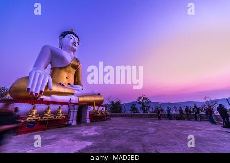 Tak, Thailand - August 5, 2017: Outdoor großen weißen Buddha Bild mit goldenen Gewändern und Mönch Statuen in den Buddhistischen Tempel, wo ist die touristische Destination i - Stockfoto