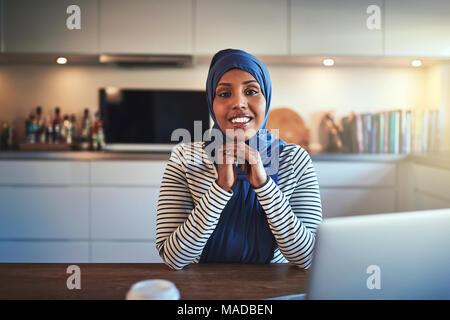 Selbstbewussten jungen Arabisch weibliche Unternehmer trägt ein Kopftuch, die an einem Notebook arbeitet, während an einem Tisch sitzen in ihrer Küche - Stockfoto