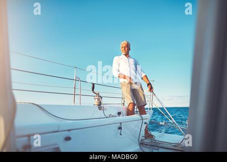 Reifen Mann an Deck eines Bootes Lenkung mit dem Seitenruder während heraus für ein Segel auf dem Ozean an einem sonnigen Tag - Stockfoto