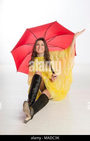 Wetter Frau gekleidet in einem gelben Poncho und hält ein rotes Dach - Stockfoto