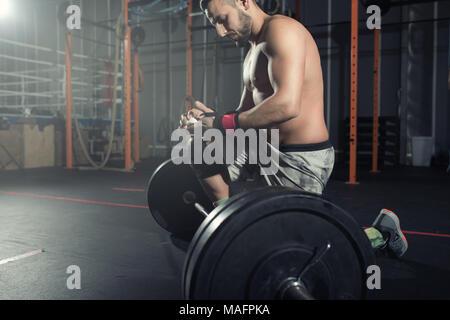 Athletischer Mann arbeitet, die an der Turnhalle mit einem barbell - Stockfoto