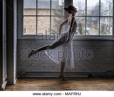 Ballerina Stretching auf einem Holzboden mit einer Mauer im Hintergrund. - Stockfoto