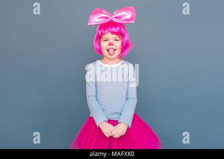 Schöne Mädchen in Clown Kostüm Witz und die Zunge raus. Studio shot, auf grauem Hintergrund - Stockfoto