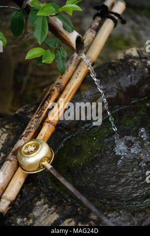 Chozubachi, Wasser Reinigung Becken mit einem Bambus Trinkschnabel und ein Wagen, mit Japanischen Wabi-Sabi Philosophie Grundsätze der Suche nach Schönheit in der Natur und - Stockfoto