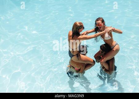 Gruppe von Frauen Spaß im Urlaub in den Pool. Mädchen spielen und genießen ihre Ferien in einem Pool. - Stockfoto