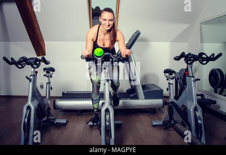 Junge Frau auf ein sich drehendes Rad an der Turnhalle. - Stockfoto
