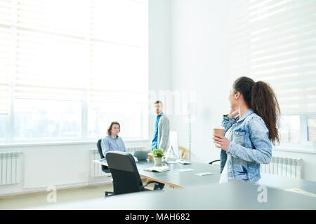 Manager Aufruf am Telefon und im Gespräch mit Kollegen - Stockfoto