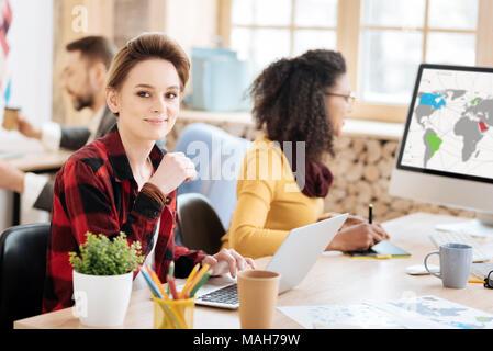 Fröhliche blonde Frau an ihrem Laptop - Stockfoto