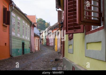 Gepflasterten Straßen führen vorbei an bunten alten Häusern zur Zitadelle in Sighisoara, Rumänien - Stockfoto