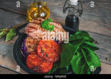 Steak selten mit dem Blut von Gemüse Tomaten und Spinat in einer Pfanne zu Hause auf dem hölzernen Tisch gegrillt. Im rustikalen Stil. - Stockfoto