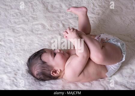 Little Baby liegend auf flauschigen weissen Blatt und ihr Bein Holding - Stockfoto