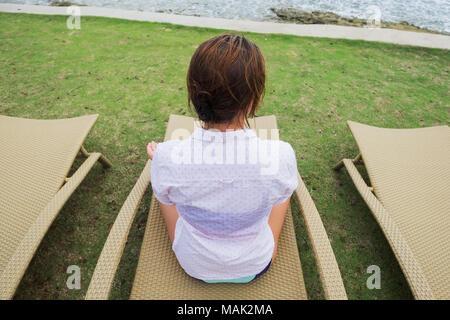 Kaukasische Frau ruhend Sitzen im Stuhl am Strand - Stockfoto