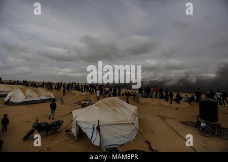 Palästinensische Demonstranten ansehen Rauchwolken, wie sie von verbrannten Reifen steigen, die israelischen Truppen abzulenken, während Auseinandersetzungen entlang der Grenzen zwischen Israel und Gaza, östlich von Khan Yunis, im südlichen Gazastreifen, 03. April 2018. Foto: Mohammed Talatene/dpa - Stockfoto