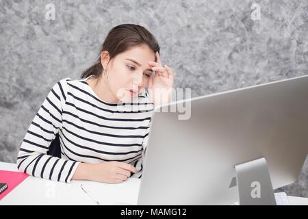Schöne junge Frau an einem Computerbildschirm und Denken im Büro, gestresst und nervös auf der Suche - Stockfoto
