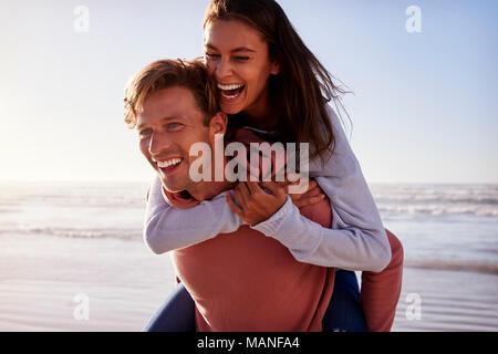 Mann, Frau, Huckepack auf Winter Urlaub am Strand - Stockfoto