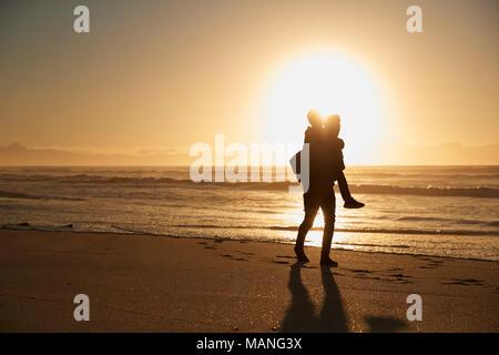 Silhouette von Vater und Sohn Huckepack auf Winter Strand - Stockfoto