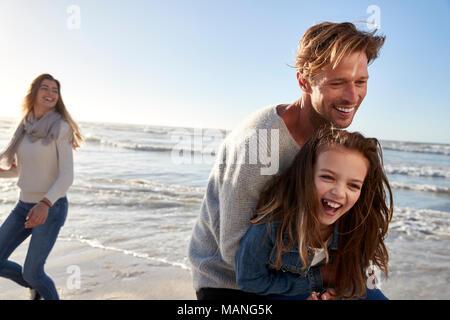 Eltern mit Tochter Spaß im Winter Beach zusammen - Stockfoto