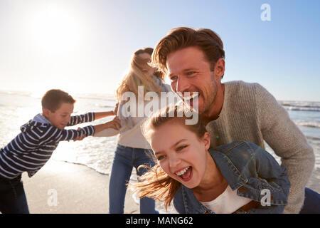 Eltern mit Kindern Spaß im Winter Beach zusammen - Stockfoto